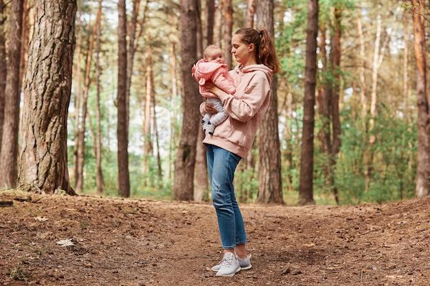 Giovane bella femmina con capelli castani e coda di cavallo che tiene in mano una bambina, che cammina insieme nel parco o nella foresta