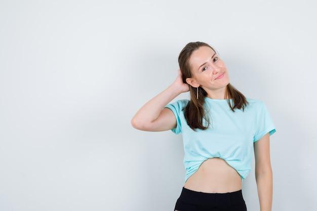 티셔츠를 입고 머리 뒤로 손을 얹고 행복한 표정을 짓고 있는 젊은 아름다운 여성.