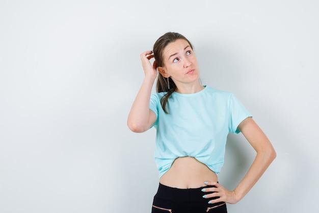 頭に手を置いて、tシャツで目をそらし、物思いにふける若い美しい女性。正面図。