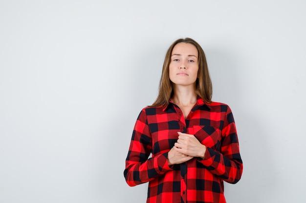 カジュアルなシャツを着て、自信を持って自分の前に手を持っている若い美しい女性。正面図。