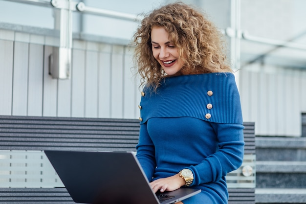 Young beautiful female with a laptop sits on a bench in the business part of the city. young beautiful woman, freelancer, works on the laptop in summer wear blue dress.