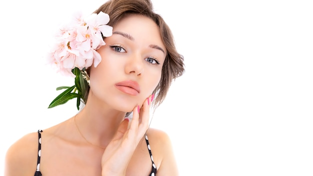 メイク、肉付きの良い唇、きれいな肌、白い背景で隔離の髪に花を持つ若い美しい女性。ピュアフレッシュな肌、唇のふくよかなコンセプト。