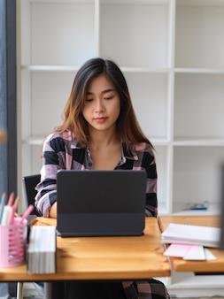 Молодая красивая женщина, работающая в современном рабочем пространстве с планшетом