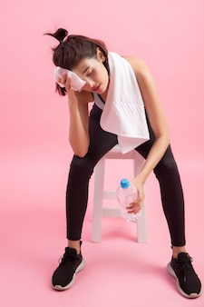 Young beautiful fit woman drinking water after exercise