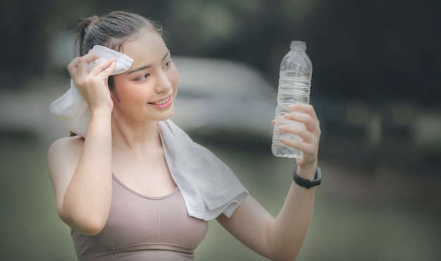 Young beautiful fit woman holding water bottle and relax after exercise, copy space.