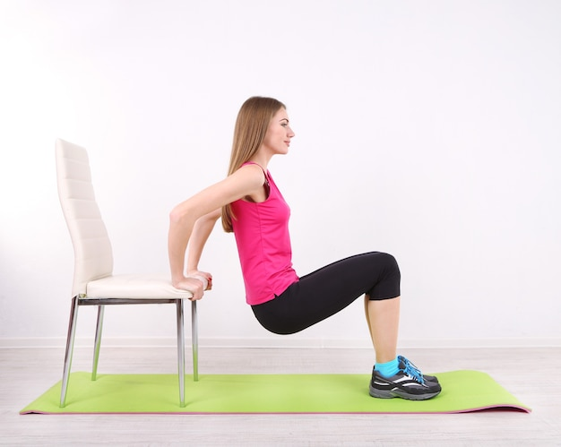체육관에서 녹색 매트에 운동 젊은 아름다운 피트니스 소녀