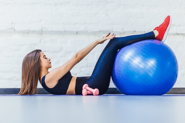 Молодая красивая девушка фитнеса работая с синим мячом в тренажерном зале.