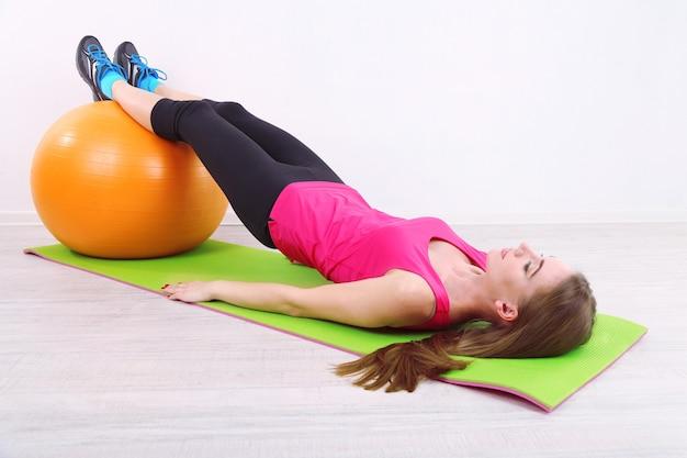 체육관에서 주황색 공을 가지고 운동하는 젊은 아름다운 피트니스 소녀