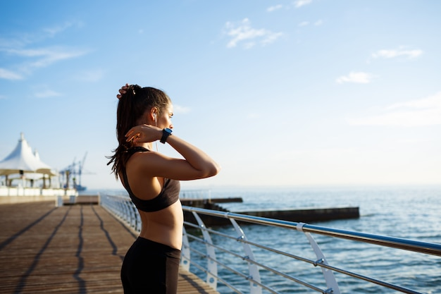 Young beautiful fitness girl makes sport exercises with sea coast on wall