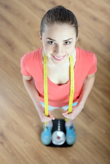 Young beautiful fitness girl standing on weight.