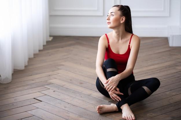 トレーニング後に床に座っている若い美しいフィットネスモデル。自宅でスポーティな女性の肖像画。