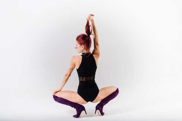 Young beautiful flexible female in a black jumpsuit and high heels is posing in a dance studio.