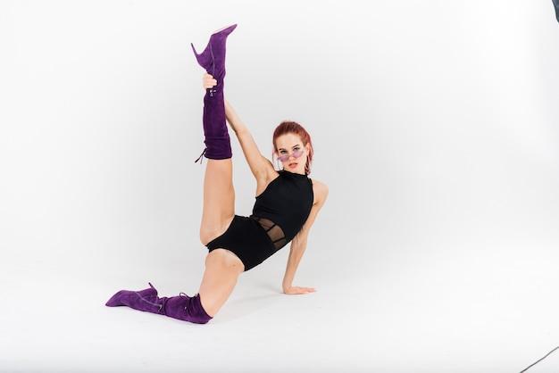 검은 점프 슈트와 하이힐에 젊은 아름다운 유연한 여성은 댄스 스튜디오에서 포즈를 취하고 있습니다.