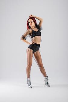 Молодая красивая гибкая девушка в черном комбинезоне и на высоких каблуках позирует в танцевальной студии.