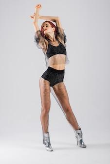 검은 죄수 복과 하이힐에 젊은 아름 다운 유연한 여성 댄스 스튜디오에서 포즈입니다.