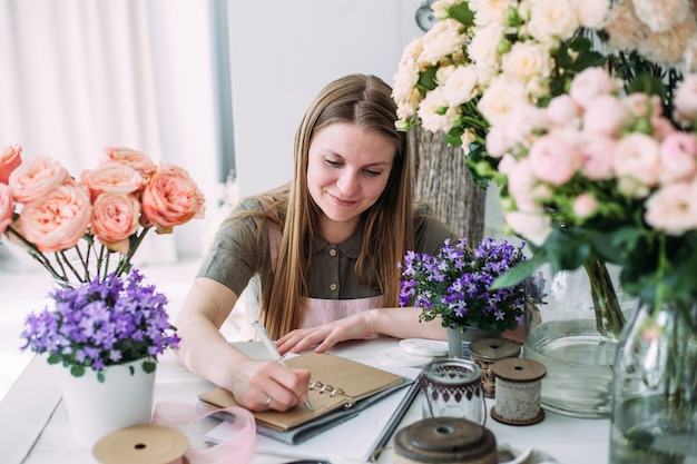Young beautiful florist in a flower shop