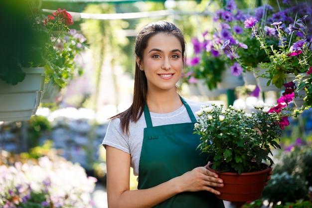Young beautiful florist posing, smiling among flowers.