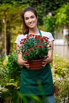 若い美しい花屋ポーズ、花の中で笑顔。