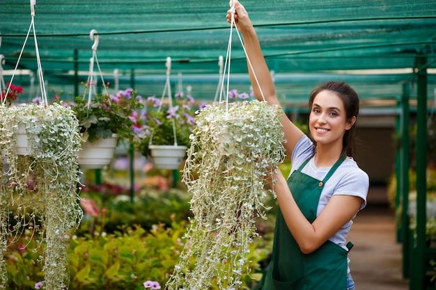 Giovane fiorista bello prendersi cura dei fiori.