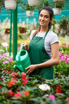 Young beautiful florist watering flowers.
