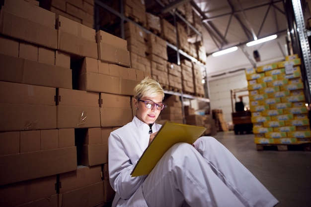 Young beautiful focused female worker is filling a paperwork on the yellow folder that is leaned against her lap while sitting on floor leaned against a stack of brown cardboard boxes in factory stora