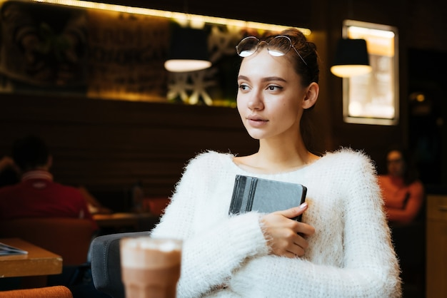 Young beautiful freelancer girl with glasses and a white sweater sits in a cafe, holds a notebook for work