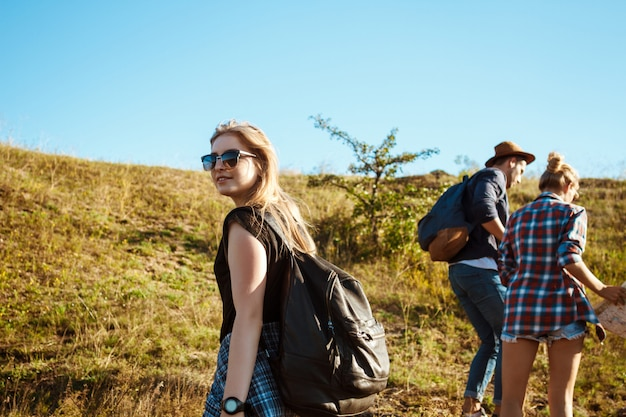 Young beautiful friends with rucksacks going up hill