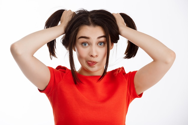 Young beautiful funny crazy brunette girl making pony-tails smiling and showing tongue over white wall