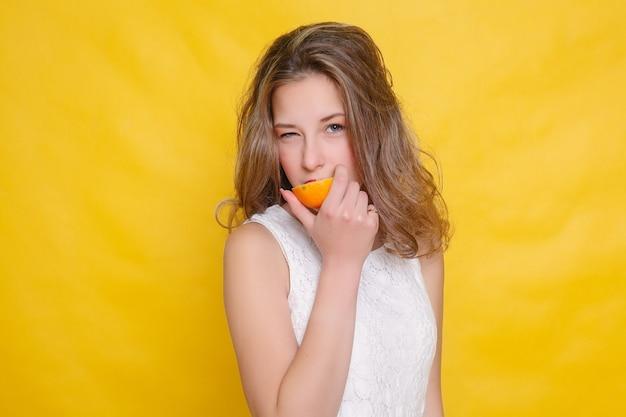 Молодая красивая забавная фотомодель с долькой апельсина на оранжевом фоне. с макияжем и прической. держит лимон с красивой улыбкой.