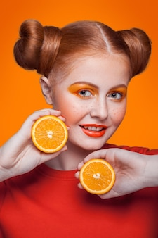 주황색 배경에 주황색 조각이 있는 젊고 아름다운 재미있는 패션 모델. 오렌지 메이크업과 헤어스타일과 주근깨. 스튜디오 촬영, 미소로 카메라를 찾고.