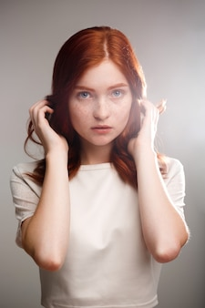 Young beautiful ginger girl over gray wall with back light.