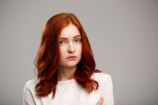 Young beautiful ginger girl over gray wall.