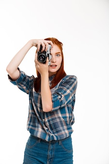 Young beautiful ginger photographer over white wall.