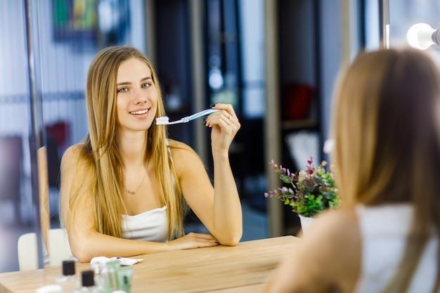 거울 앞에서 이를 닦으려는 아름다운 소녀