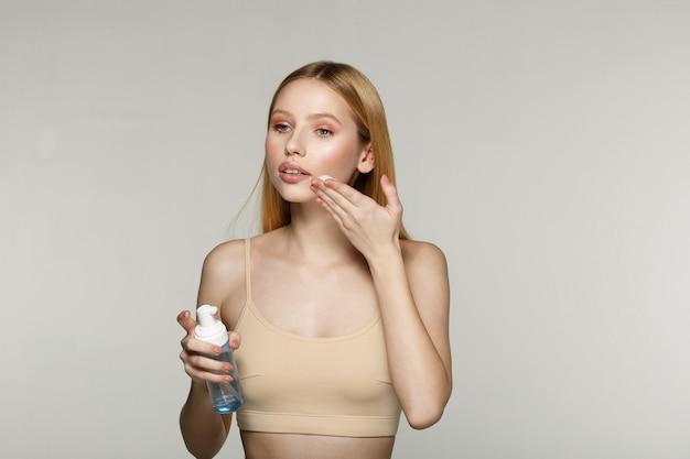 얼굴에 화장품 크림을 적용하는 젊은 아름 다운 소녀