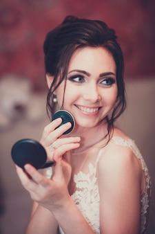 Young beautiful girl applying make up