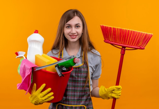 Young beautiful girl in apron holding bucket with cleaning tools and mop smiling cheerfully