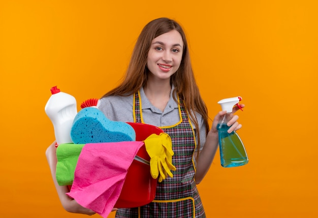 Young beautiful girl in apron holding bucket with cleaning tools and spray smiling cheerfully