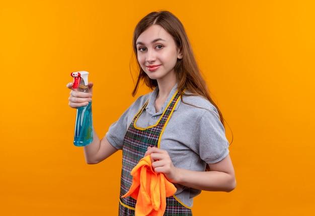 Giovane bella ragazza in grembiule azienda spray per la pulizia e tappeto guardando sorridente della fotocamera, pronta per la pulizia