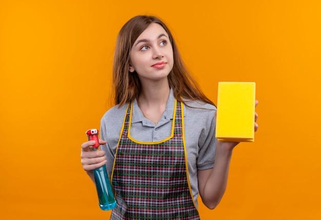 Giovane bella ragazza in grembiule che tiene spray per la pulizia e spugna che guarda da parte con sguardo sognante sorridente
