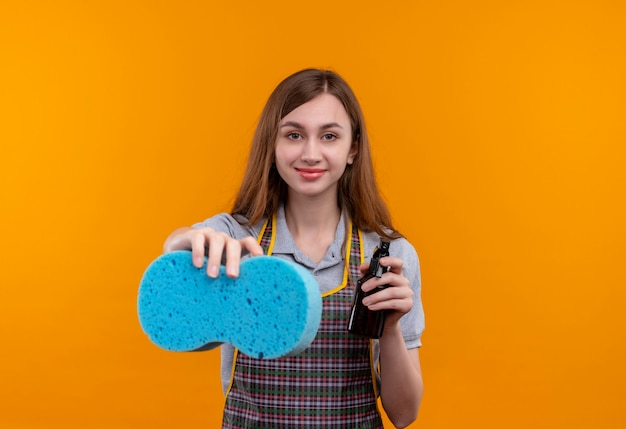 Giovane bella ragazza in grembiule che tiene pulizia spray e spugna guardando sorridente della fotocamera, pronta per la pulizia