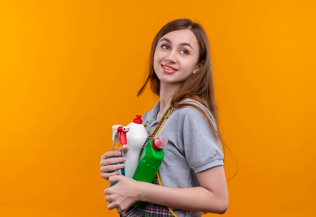 Young beautiful girl in apron holding cleaning supplies looking aside smiling friendly, ready for cleaning