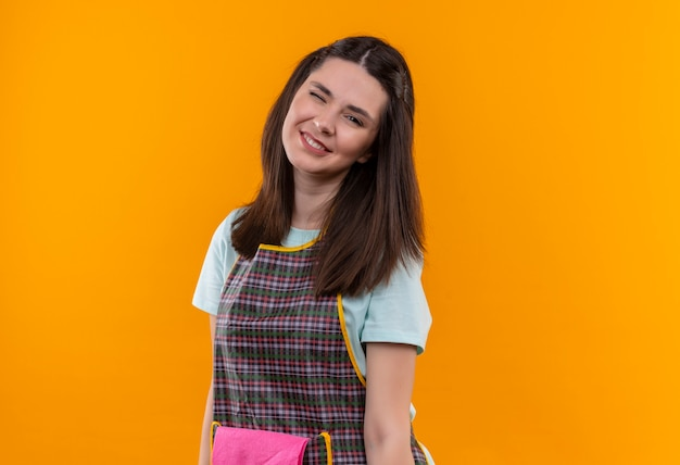 Young beautiful girl in apron looking at camera smiling and winking