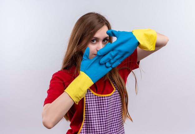Giovane bella ragazza in grembiule e guanti di gomma che copre il viso con le mani che guarda l'obbiettivo con viso serio