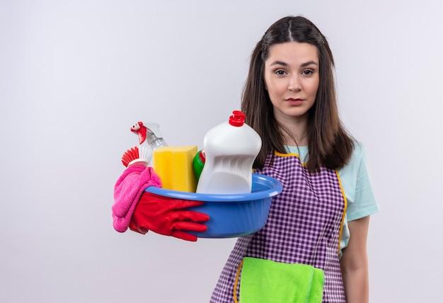 Giovane bella ragazza in grembiule e guanti di gomma che tiene bacino con strumenti di pulizia che guarda l'obbiettivo stanco e annoiato