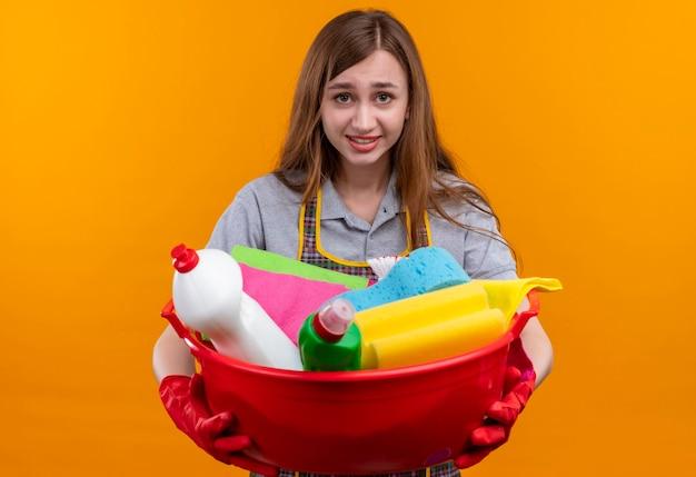 Giovane bella ragazza in grembiule e guanti di gomma che tiene bacino con strumenti di pulizia che guarda alla telecamera con un sorriso scettico sul viso