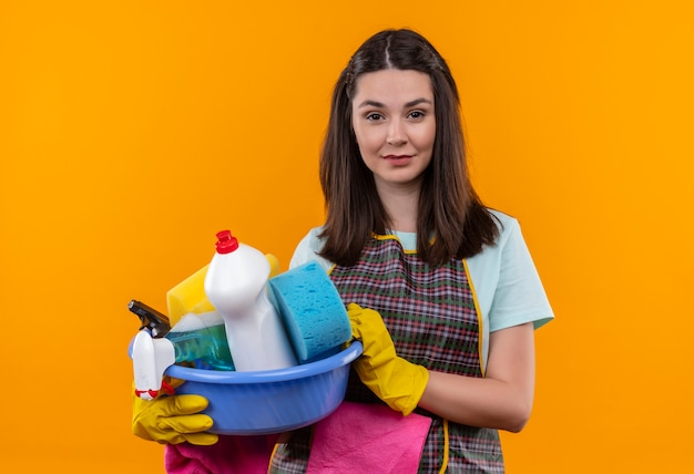 Young beautiful girl in apron and rubber gloves holding basin with cleaning tools smiling friendly looking at camera