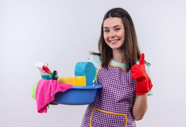 Giovane bella ragazza in grembiule e guanti di gomma che tengono bacino con strumenti di pulizia che sorride con la faccia felice che mostra i pollici su