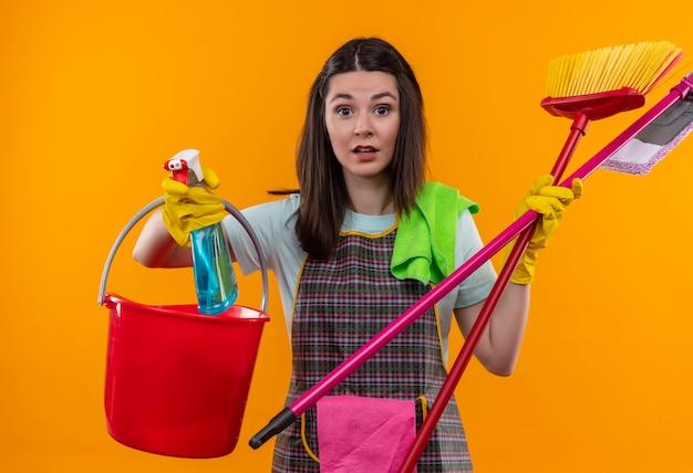 Giovane bella ragazza in grembiule e guanti di gomma che tengono secchio e strumenti di pulizia che sembrano confusi e sorpresi
