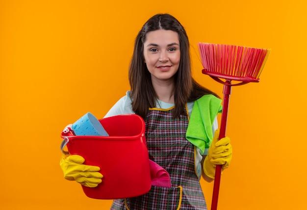Giovane bella ragazza in grembiule e guanti di gomma che tengono secchio e scopa sorridente fiducioso, concetto di lavori domestici